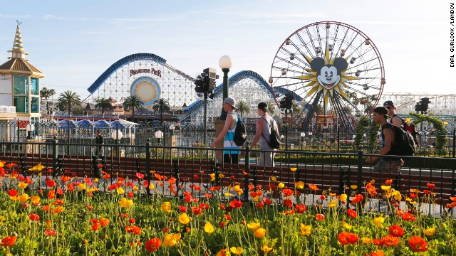 Image #: 28794655    People walk on the Paradise Pier as Mickey's Fun Wheel and the  California Screamin' roller coaster sit in the background at Disney's California Adventure park on April 8, 2014 in Anaheim, California.    Earl Gurlock /Landov