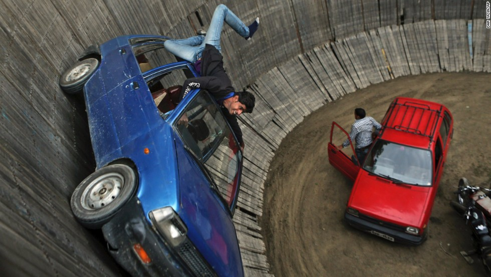 "A stunt driver performs at the ""Well of Death"" exhibition in Srinagar, India, on Friday, May 23. Motorcycles are also driven around the vertical walls."