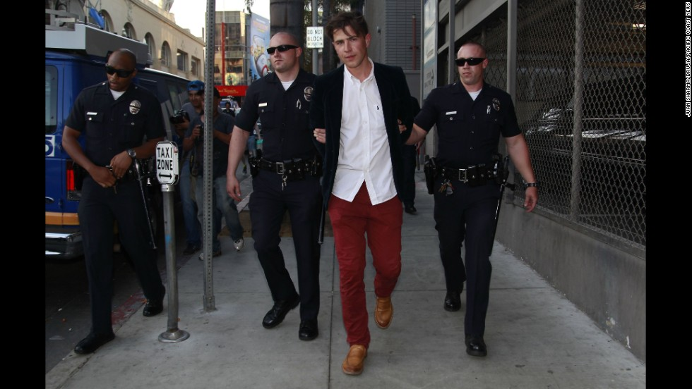 "Ukrainian television reporter <a href=""http://www.cnn.com/2014/05/29/showbiz/gallery/vitalii-sediuk/index.html"">Vitalii Sediuk</a> is taken away in handcuffs after allegedly striking actor Brad Pitt in the face as Pitt walked the red carpet at the ""Maleficent"" premiere in Hollywood, California, on Wednesday, May 28. Sediuk has a history of confronting celebrities at red carpet events."