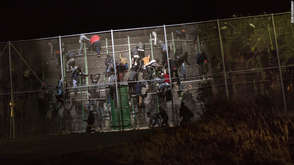 Sub-Saharan migrants scale a metallic fence that divides Morocco and the Spanish enclave of Melilla on Wednesday, May 28. Several hundred migrants charged the border fence, with many managing to get across while others were beaten back by police.