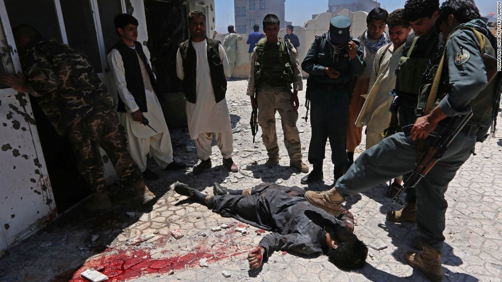 "An Afghan policeman kicks the body of a dead gunman who officials say was one of four people trying to <a href=""http://www.cnn.com/2014/05/23/world/asia/afghanistan-violence/index.html"">attack the Indian consulate</a> in Herat, Afghanistan, on Friday, May 23. The attackers were eventually surrounded by security forces as they approached the consulate. The consulate wasn't damaged, and no one there was injured."