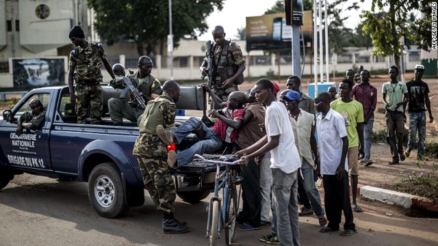 Members of the Central African Republic's National Gendarmerie help to carry a wounded civilian off his bike onto a truck heading to the hospital in the central district of Bangui on May 29, 2014. At least 15 people, including a priest, were killed and several others wounded in clashes on the eve in the capital of the strife-torn Central African Republic, a military source said. AFP PHOTO/MARCO LONGARIMARCO LONGARI/AFP/Getty Images