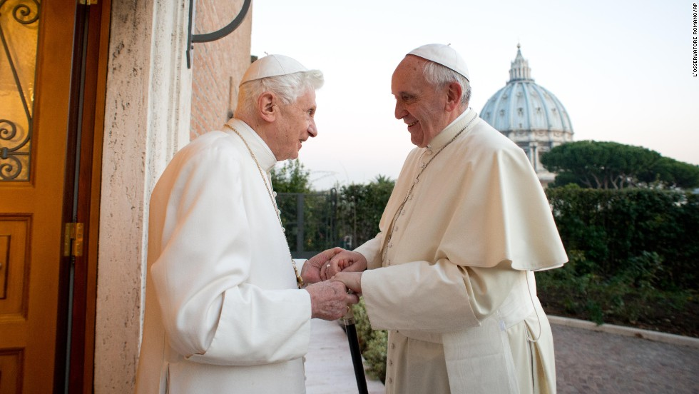 Pope Emeritus Benedict XVI, left, greets his successor, Pope Francis, in December 2013. Earlier in the year, Benedict became the first pope to resign in nearly six centuries.