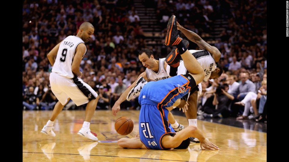 Steven Adams of the Oklahoma City Thunder flips over on his head as he goes for a loose ball near three San Antonio Spurs on Thursday, May 29. The Spurs won the game and eventually the series, earning them an NBA Finals rematch against the Miami Heat.