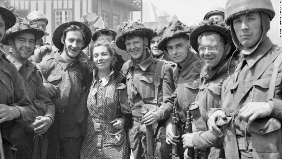 British troops pose for a photograph with a French woman in La Breche d'Hermanville.