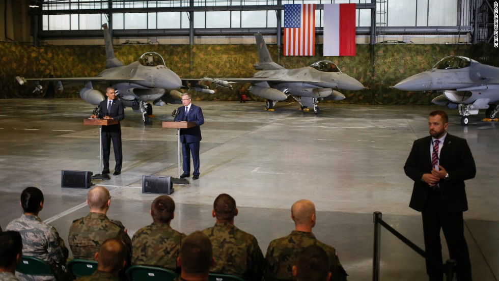 A Polish security official, right, stands watch as Obama and Komorowski make statements after meeting U.S. and Polish troops at an event in Warsaw on June 3. The main focus of Obama's Poland visit comes Wednesday, June 4, when he will give a speech  25 years after the nation's historic elections of 1989.