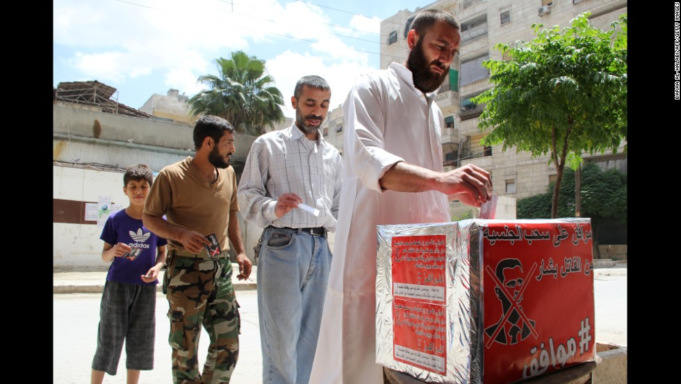 Men in Aleppo, Syria, pretend they are casting their votes June 3 during a mock election calling for al-Assad to the stripped of his Syrian nationality.