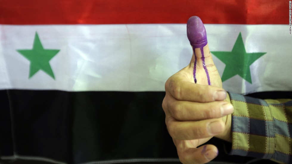 A Syrian man shows his ink-stained thumb after he voted in Homs on June 3.