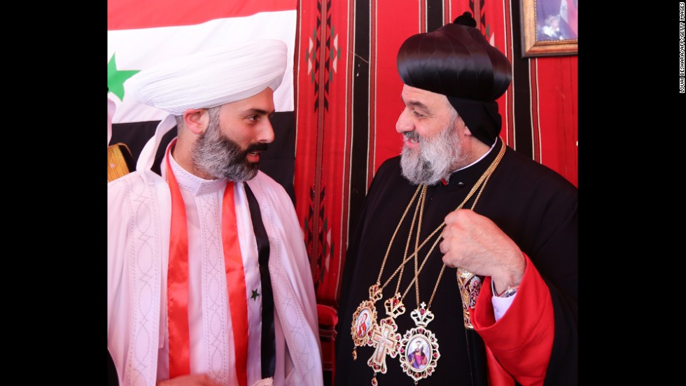 Ignatius Aphrem II, head of the Syriac Orthodox Church, right, arrives to vote in Damascus on June 3.
