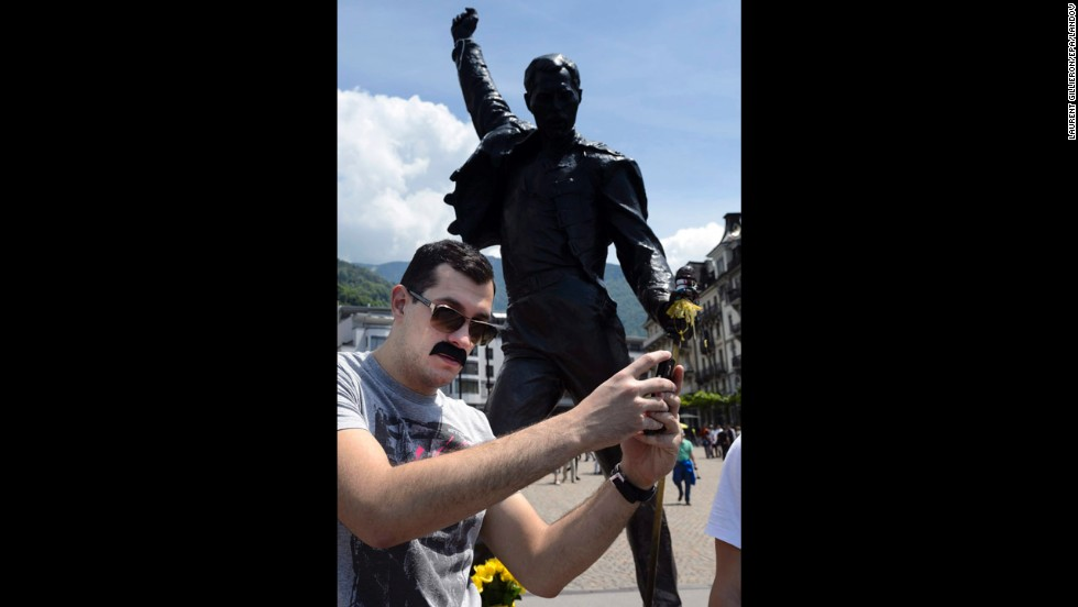 A man with a Freddie Mercury-like mustache snaps a selfie in front of a bronze statue of the late Queen singer Sunday, June 1, in Montreux, Switzerland. Mercury once lived in Montreux, which was hosting a Freddie for a Day festival to raise money for AIDS awareness.