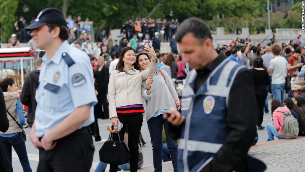 "Two women take a selfie together as Turkish policemen stand guard near Gezi Park in Istanbul's Taksim Square on Saturday, May 31. Taksim Square was the flashpoint of anti-government demonstrations last year. Activists called for more protests on the one-year anniversary, but the park <a href=""http://www.cnn.com/2014/05/31/world/europe/turkey-cnn-reporter-harassed/index.html"">was closed off</a> by police."