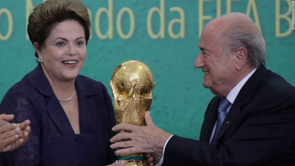 FIFA President Sepp Blatter, right, presents the 2014 World Cup trophy to Brazil's President Dilma Rousseff, during a ceremony at the Planalto presidential palace, in Brasilia, Brazil on June 2, 2014.