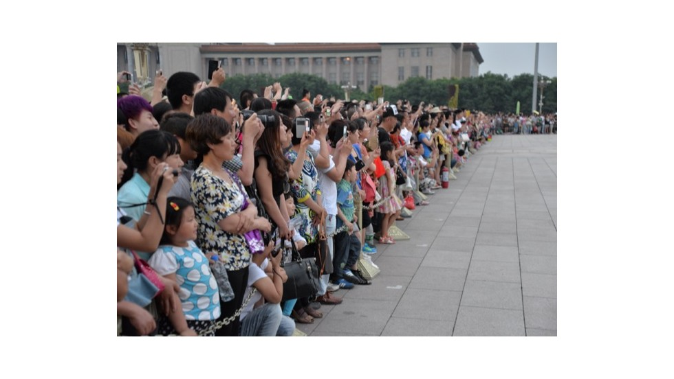 Tourists in Beijing take photos of the daily flag lowering ceremony at Tiananmen Square on June 4.