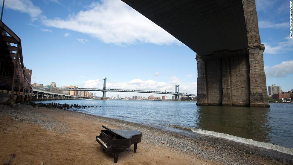 A grand piano sits by the East River, underneath the Brooklyn Bridge in New York City on Saturday, May 31. Locals aren't sure how it got there, and the mystery has inspired many to post pictures of it online. Did the piano wash ashore like that, perfectly upright? Or did someone place it there?