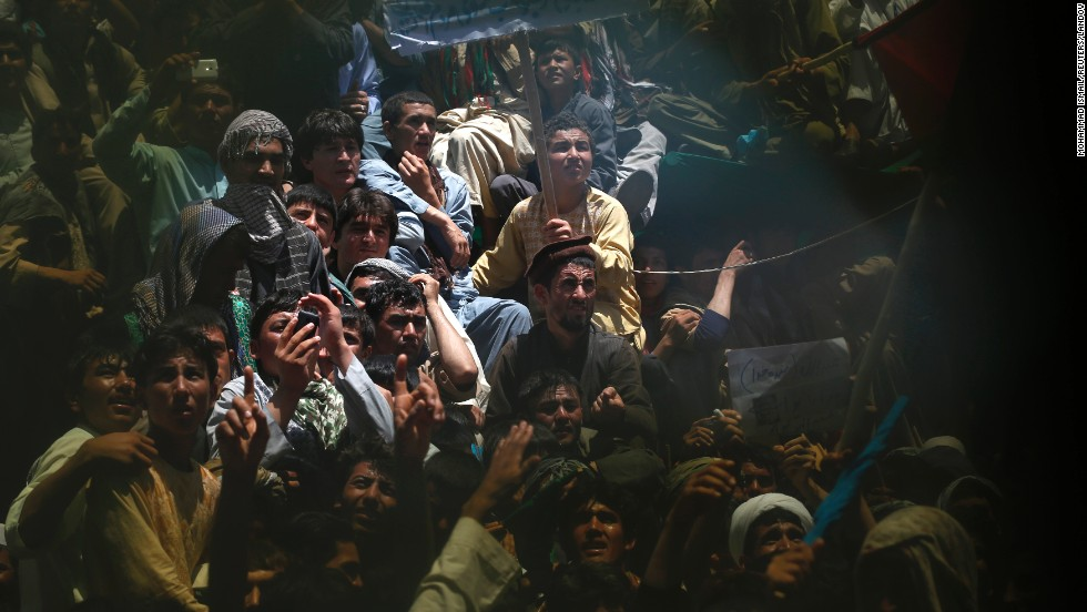 Supporters of Afghan presidential candidate Abdullah Abdullah are seen through a broken window during a campaign event in Qala i Naw, Afghanistan, on Monday, June 2. The second round of the presidential election will take place on June 14.
