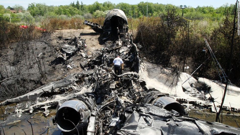 "An official with the National Transportation Safety Board looks through the wreckage where a private plane <a href=""http://www.cnn.com/2014/06/01/us/massachusetts-plane-crash/"">crashed during takeoff</a> Saturday, May 31, in Bedford, Massachusetts. Seven people were killed, including prominent businessman and philanthropist Lewis Katz."