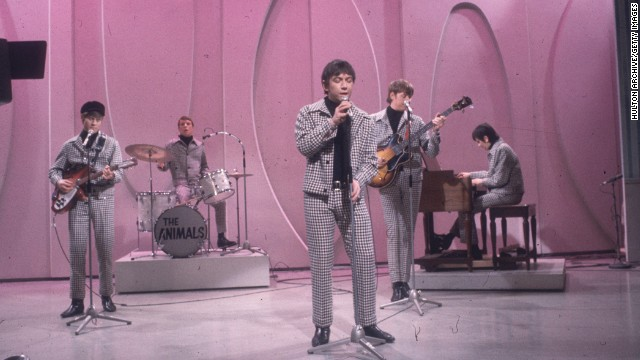 1966:  Full-length view of the British rock group The Animals, wearing matching checkered coats and black turtlenecks, performing on the set of a television program with a lavender backdrop. Lead singer Eric Burdon stands in the forefront.  (Photo by Hulton Archive/Getty Images)