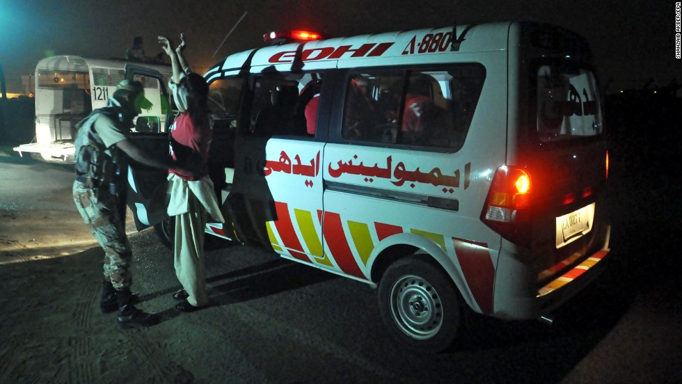 Pakistani rangers check ambulance staff at a boundary wall at the airport on June 8.