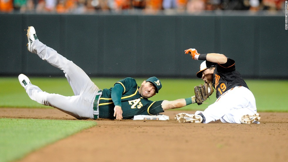 Oakland's Nick Punto stretches to tag Baltimore's Chris Davis during a slide into second base Friday, June 6, in Baltimore. Oakland won the game 4-3.