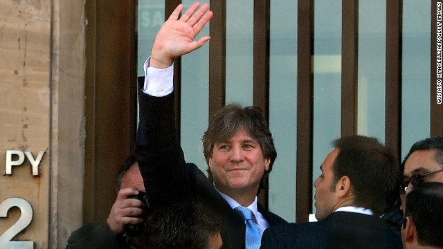Argentine Vice President Amado Boudou waves upon arrival at Comdoro Py court for questioning about alleged influence-peddling in the acquisition of a company with a monopoly to print the national currency, in Buenos Aires, on June 9, 2014. The case, which marks the first time a sitting Argentine vice president has been taken to court, stems from a transaction in 2010 when Boudou was the country's economy minister.