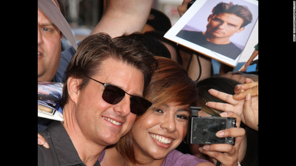 "Actor Tom Cruise takes a photo with a fan in New York on Thursday, June 5. He was there to appear on ""The Daily Show with Jon Stewart."""