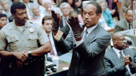 O.J. Simpson looks at a new pair of Aris extra-large gloves which the prosecutors had him put on for the jury 21 June 1995 during his double murder trial in Los Angeles. The gloves were the same type found at the Bundy murder scene and the O.J. Simpson estate.     AFP PHOTO VINCE BUCCI        (Photo credit should read VINCE BUCCI/AFP/Getty Images)