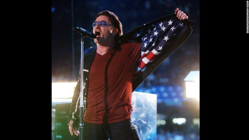 Bono, the lead singer of U2, shows an American flag design inside his jacket as the band performs during the Super Bowl halftime show in 2002.