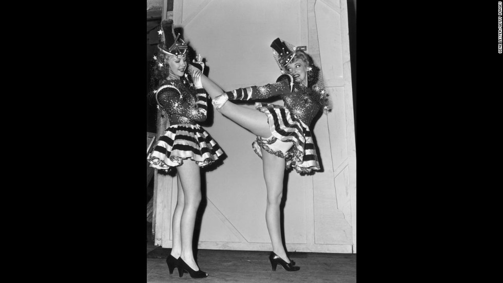 A showgirl stretches her leg on another's shoulder as they warm up backstage for a performance of the Hollywood Group Caravan in 1943. The Hollywood Group Caravan included a group of celebrities who toured U.S. cities to raise funds for the Army and Navy relief effort during World War II.