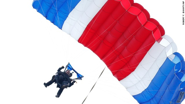 Former President George H.W. Bush, strapped to Sgt. 1st Class Mike Elliott, a retired member of the Army's Golden Knights parachute team, float to the ground during a tandem parachute jump near Bush's summer home in Kennebunkport, Maine, Thursday, June 12, 2014. Bush made the jump, his eighth, in celebration of his 90th birthday. (AP Photo/Robert F. Bukaty)