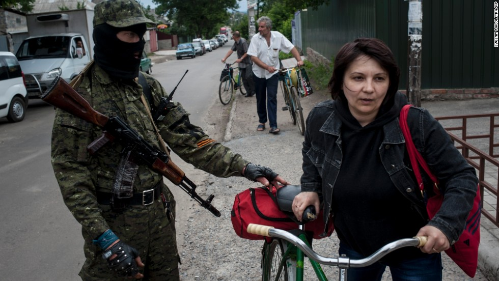 A pro-Russian fighter in Slovyansk checks a woman's documents as she leaves the city on Thursday, June 12.