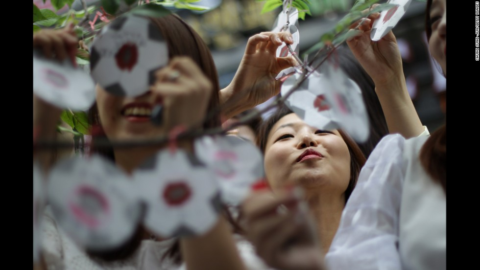 Women attach paper messages on a tree in Seoul, South Korea. The messages wish the national team success in the World Cup.