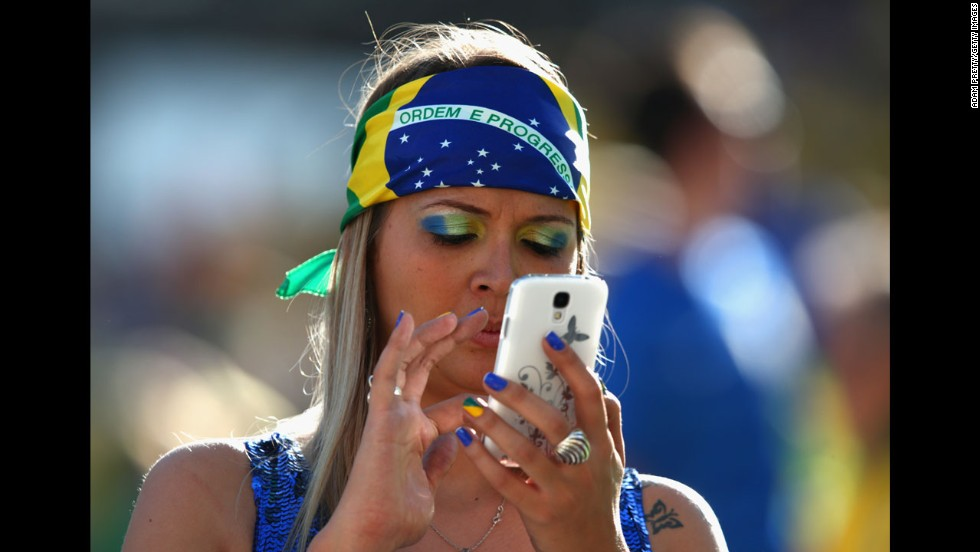 A Brazil fan uses a cell phone before the opening ceremony.