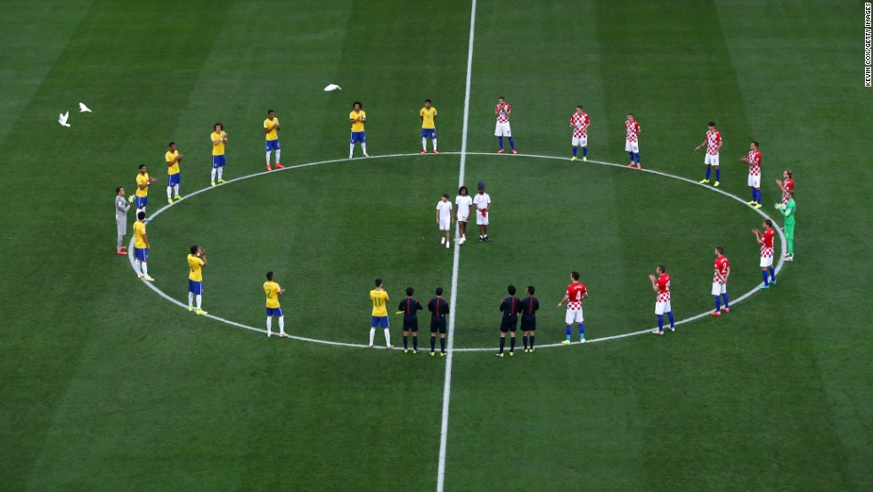 "Soccer players from Brazil and Croatia stand around the center circle of the field as doves are released prior to the opening match of the World Cup on Thursday, June 12, in Sao Paulo, Brazil. Brazil, the host country, <a href=""http://www.cnn.com/2014/06/12/football/gallery/world-cup-0612/index.html"">won the match</a> 3-1 behind two goals from star forward Neymar."