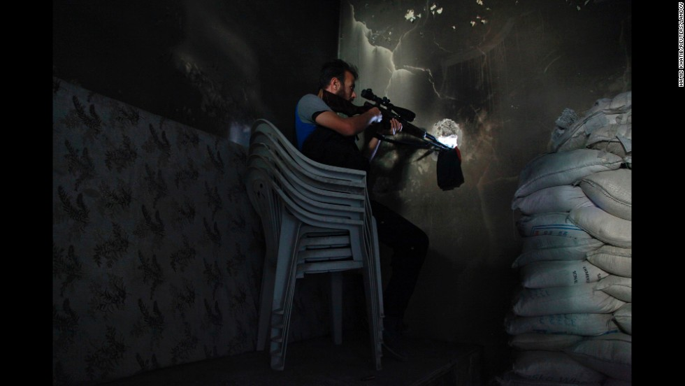 A sniper with the Free Syrian Army sits in a shooting position in Aleppo, Syria, on Saturday, June 7.