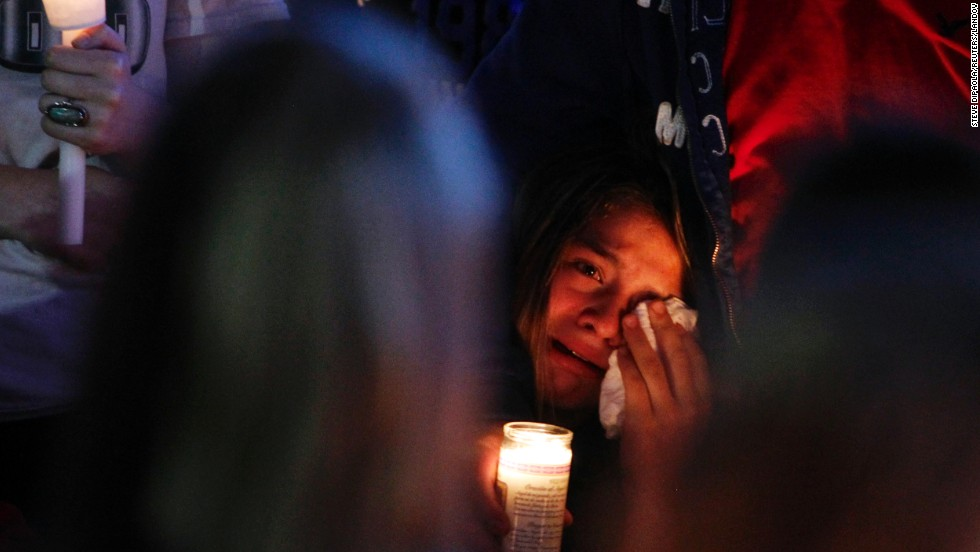"A mourner wipes away tears at a candlelight vigil after a <a href=""http://www.cnn.com/2014/06/11/justice/oregon-high-school-shooting/index.html"">shooting took place</a> Tuesday, June 10, at Reynolds High School in Troutdale, Oregon. Jared Padgett, a 15-year-old student at the school, shot and killed another student, 14-year-old Emilio Hoffman, before taking his own life, law enforcement sources said. Padgett also shot and wounded a teacher."