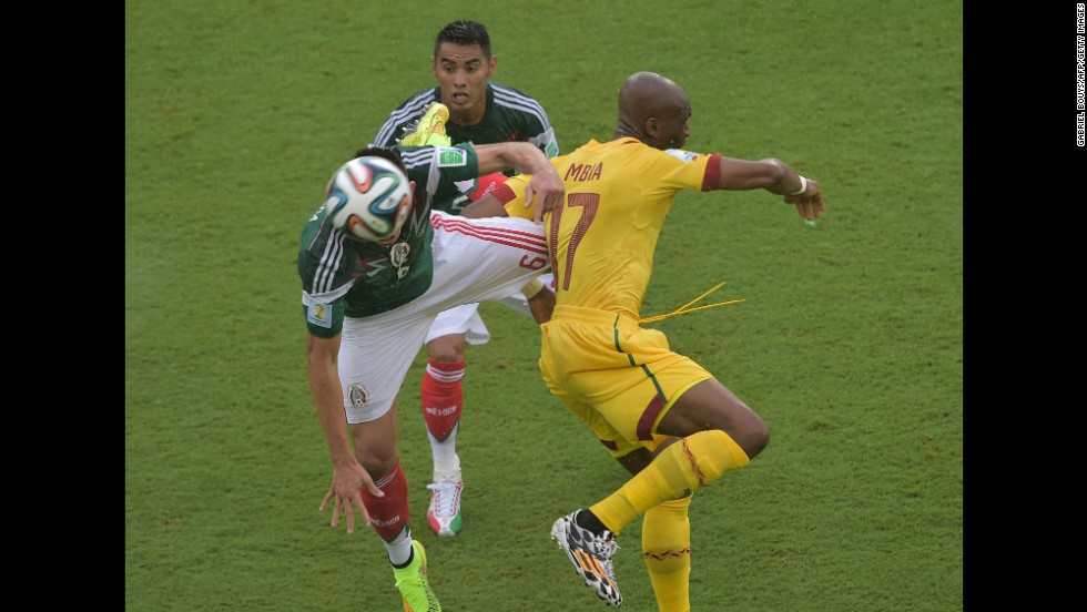 Mbia challenges Mexico midfielders Herrera, left, and Vazquez.