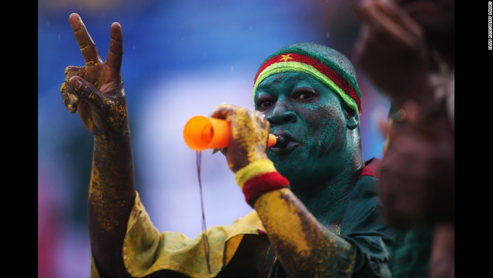 A Cameroon fan blows a horn during the match.