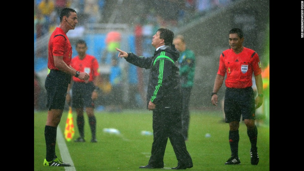 Mexican coach Miguel Herrera, center, speaks to referee Wilmar Roldan during the game. Two Mexican goals were disallowed in the first half after being called offside.