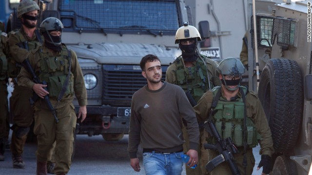 Israeli soldiers looking for three teenagers arrest a Palestinian man in the West Bank city of Hebron on Saturday, June 14.