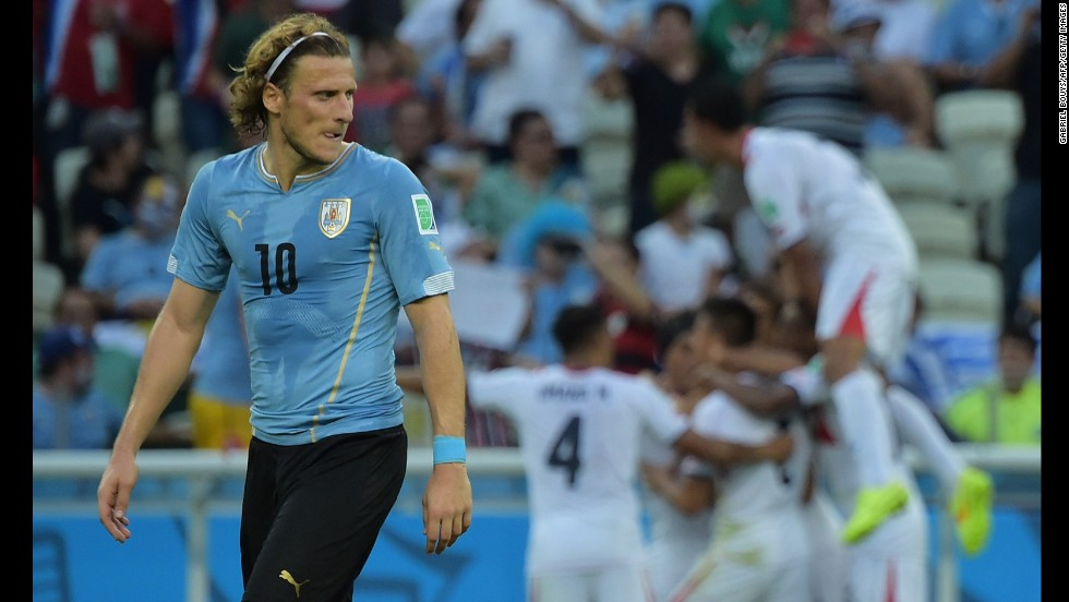 Uruguay forward Diego Forlan looks rueful as Costa Rica's players celebrate a goal in the background.