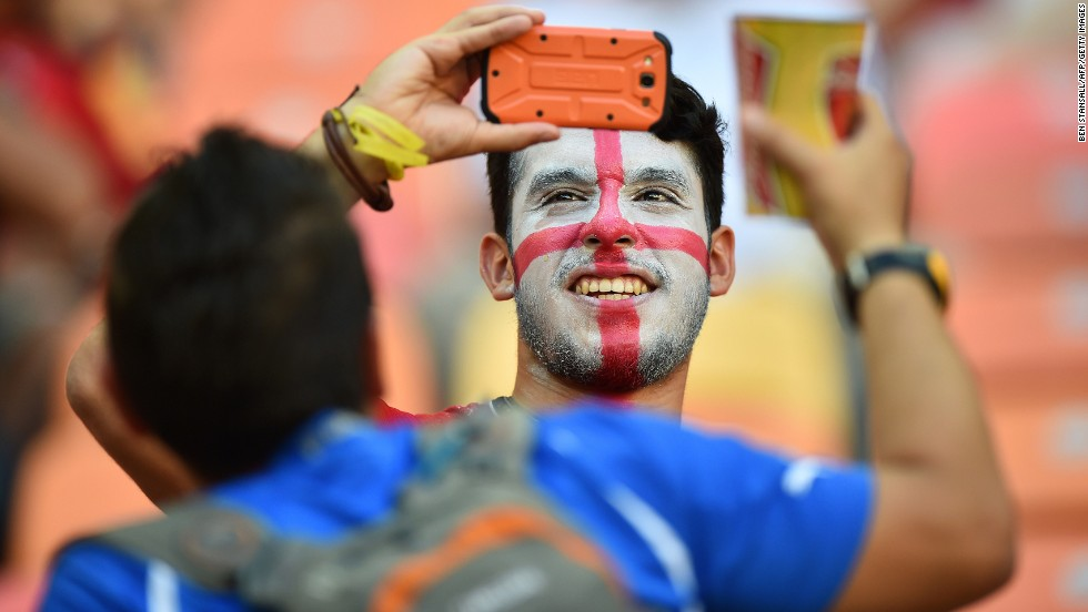 An England supporter takes pictures prior to the start of the match.