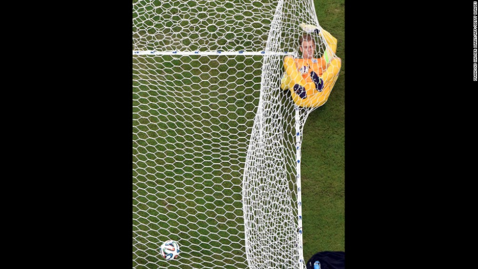 English goalkeeper Joe Hart lies in the net after Italy's Mario Balotelli scored a goal to put Italy up 2-1 in a World Cup match Saturday, June 14, in Manaus, Brazil. Italy would go on to win by that score.