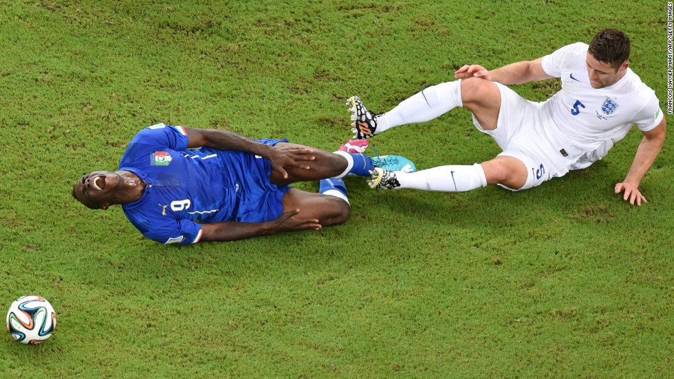 Italy forward Mario Balotelli, left, reacts following a tackle by England defender Gary Cahill.