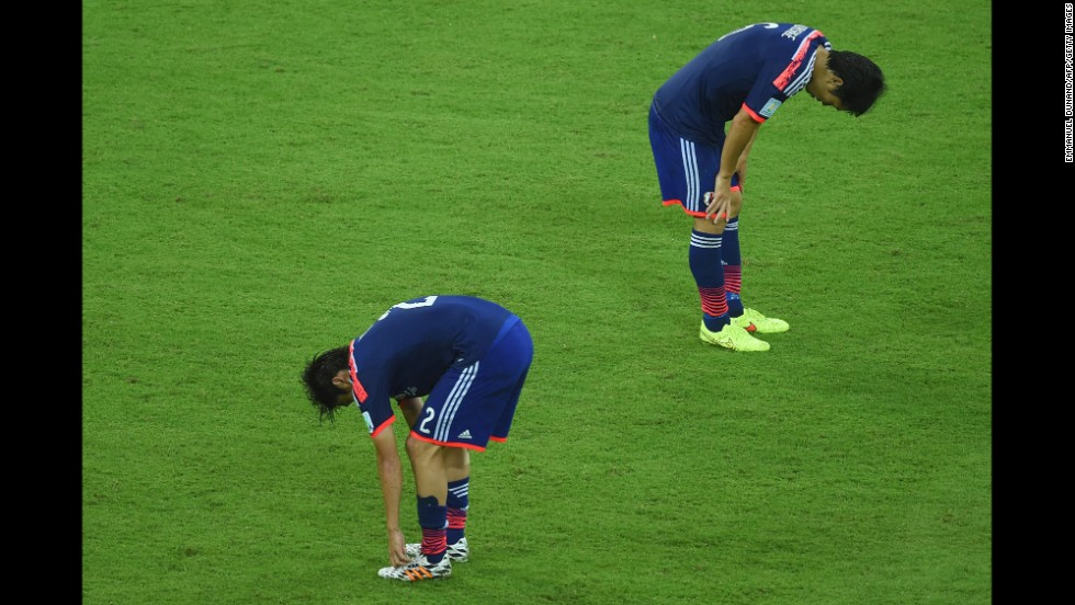 Japan players hang their heads after tough loss to Ivory Coast.
