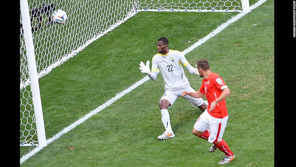 Substitute Haris Seferovic, right, scores Switzerland's injury-time winner past Ecuador goalkeeper Alexander Dominguez in the World Cup Group E match at Estadio Nacional on June 15 in Brasilia, Brazil.
