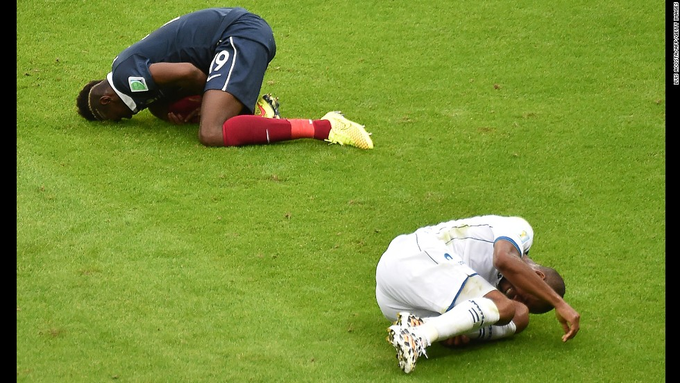 France midfielder Paul Pogba, left, and Honduras' Wilson Palacios fall after a tackle.