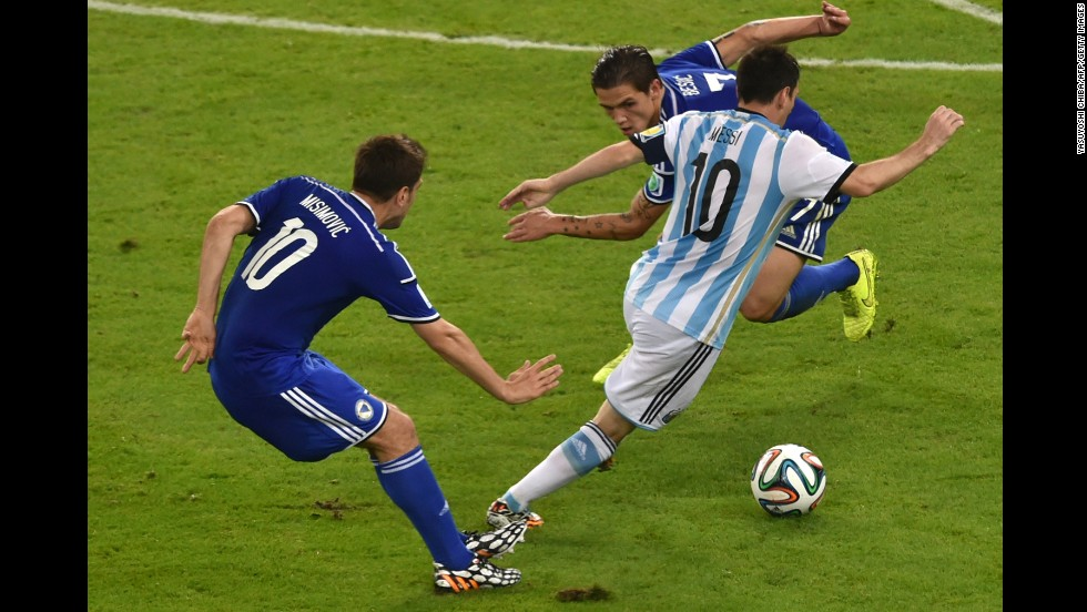 Lionel Messi, center, dribbles the ball past Bosnia-Herzegovina midfielder Zvjezdan Misimovic, left, and defender Muhamed Besic.