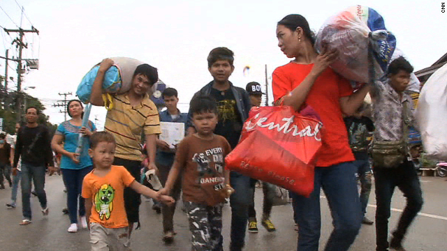 Cambodian workers gathered their belongings and their children to make the journey back to their home country.