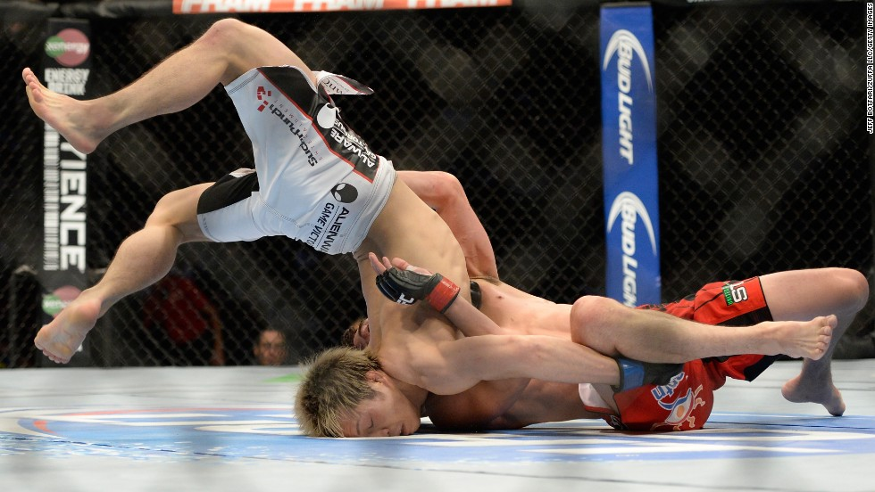 Michinori Tanaka is flipped over by Roland Delorme during the UFC 174 event in Vancouver, British Columbia, on Saturday, June 14. Tanaka won the bantamweight bout by unanimous decision.