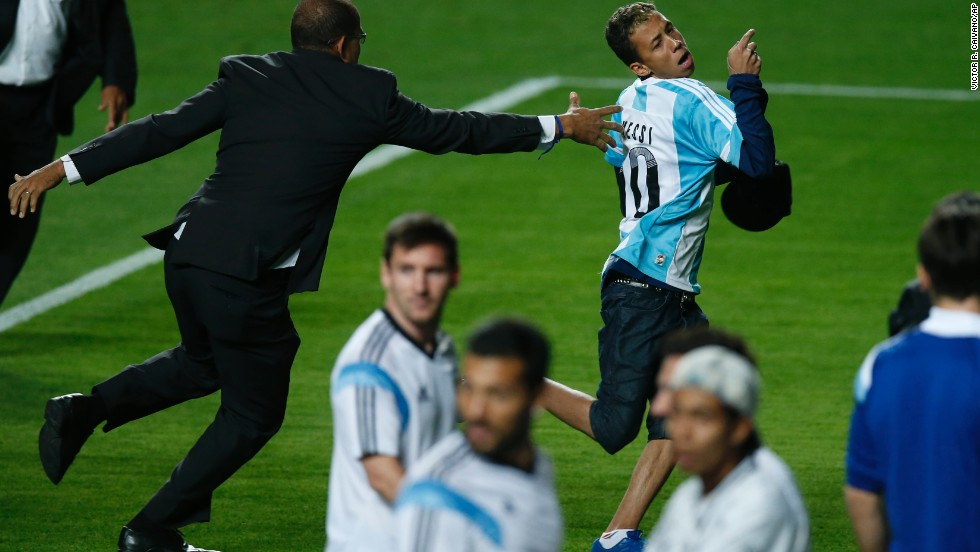A security guard tries to stop an Argentina fan who invaded the field during a training session in Belo Horizonte, Brazil, on Wednesday, June 11.